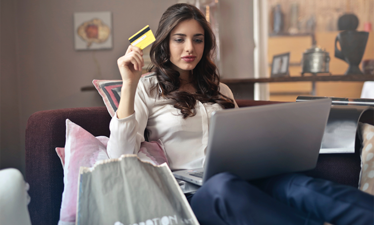 Women sitting on couch with payment card