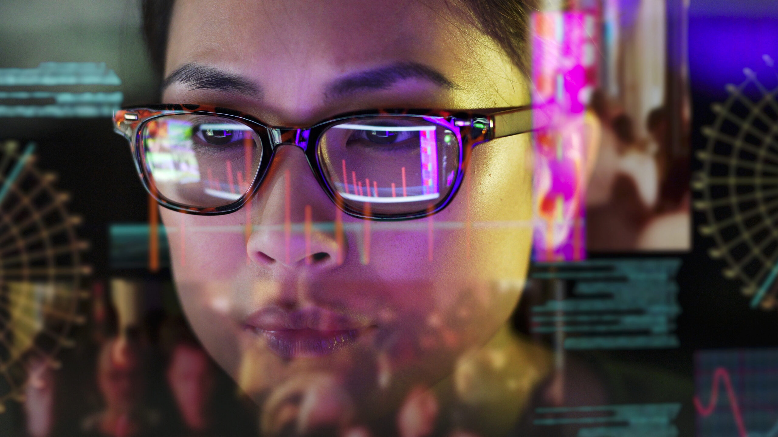 Close up stock photo of an Asian woman carefully studying computer data