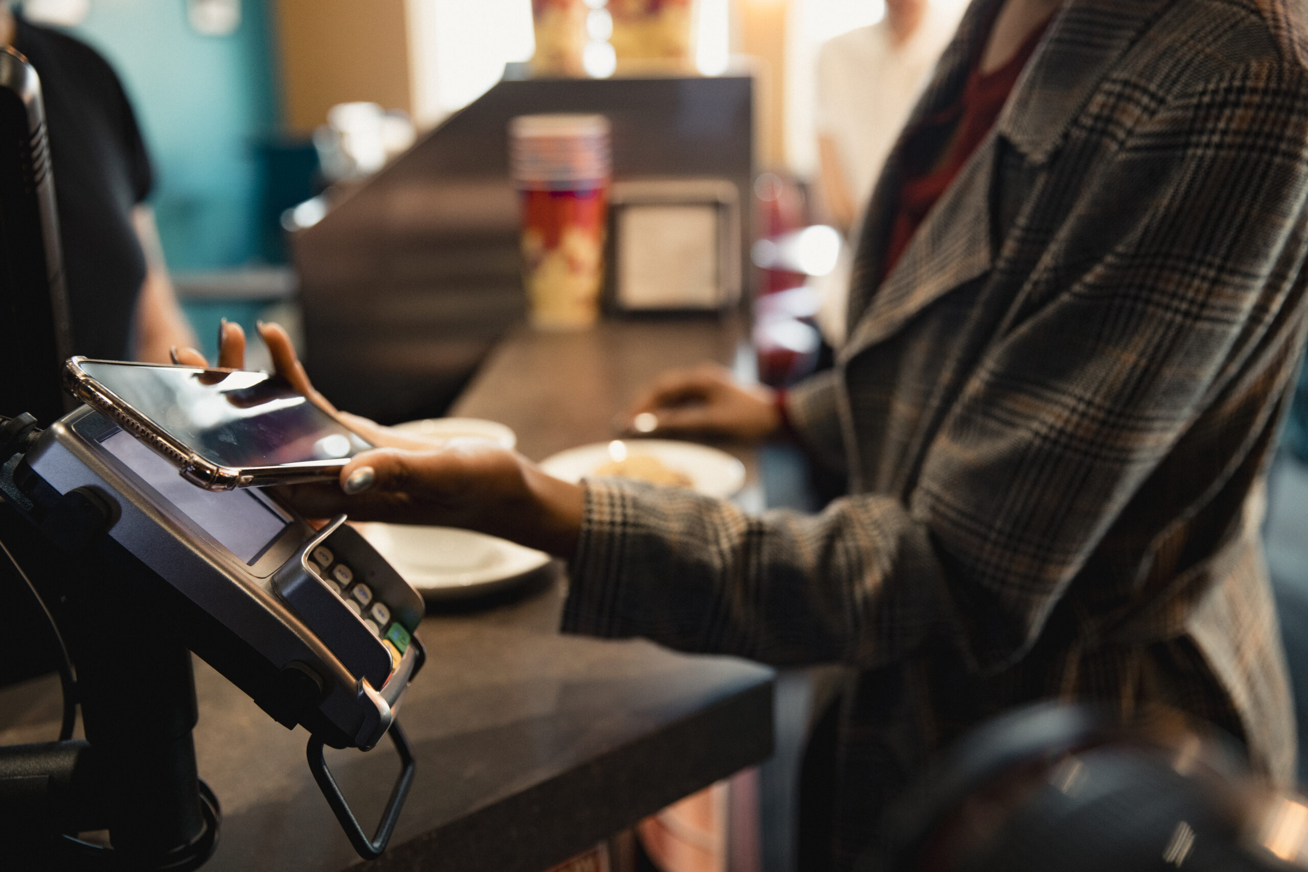 Woman at store paying for item with phone