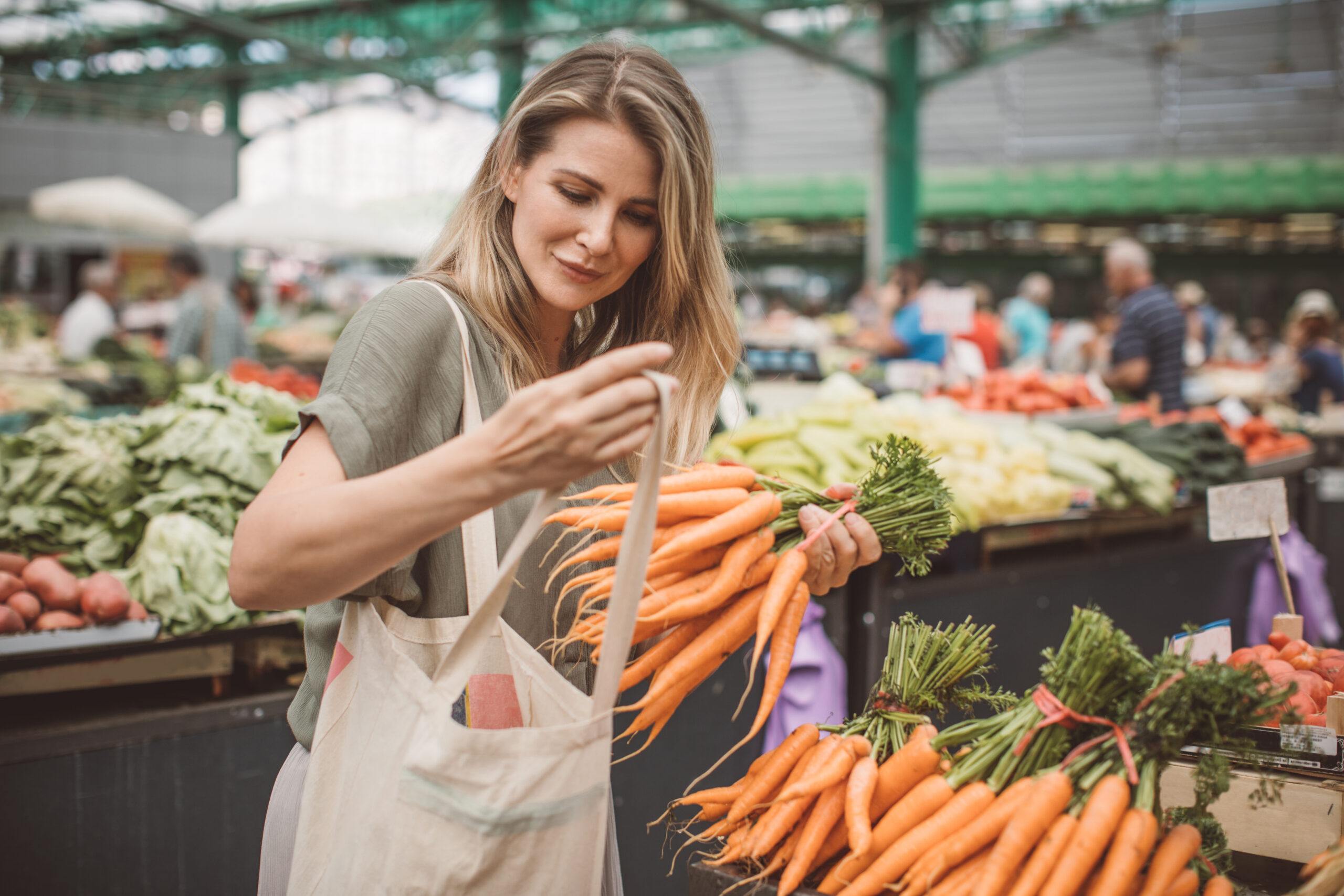 cheerful woman selecting fresh vegetables in market